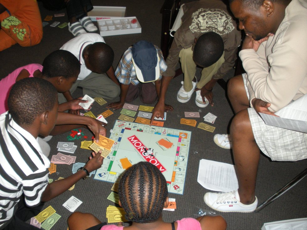 Teen Club members playing Monopoly with a Barclays staff member.