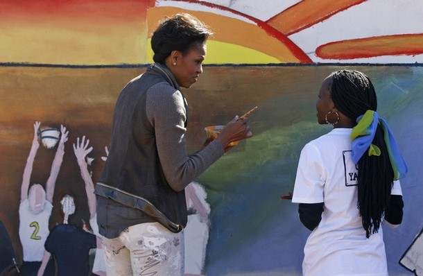 U.S. first lady Michelle Obama paints a mural with youths at Botswana-Baylor Adolescent Center in Gaborone